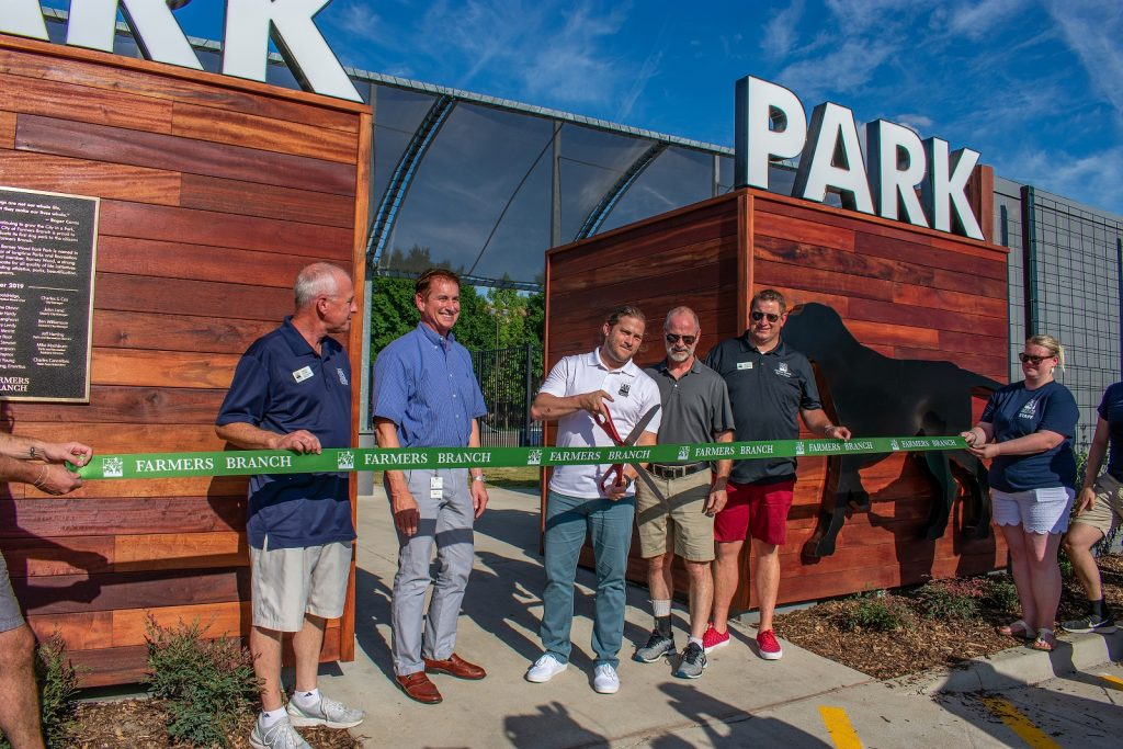Mayor Robert Dye cutting the ribbon at the Barney Wood Bark Park grand opening in Farmers Branch.